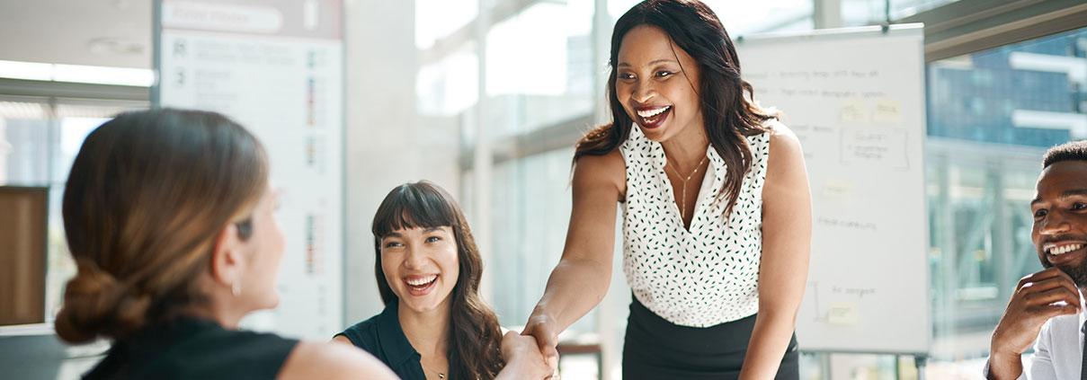 Female coworkers shaking hands in an office