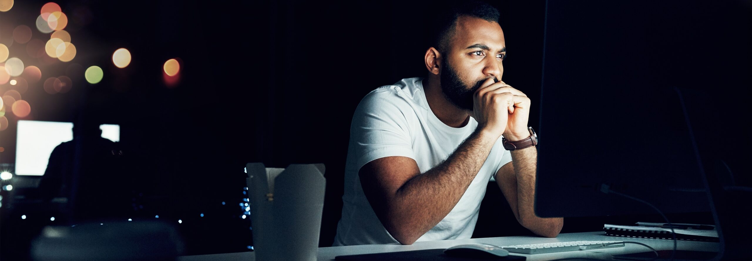 man in white shirt looking intently at computer screen in dark room
