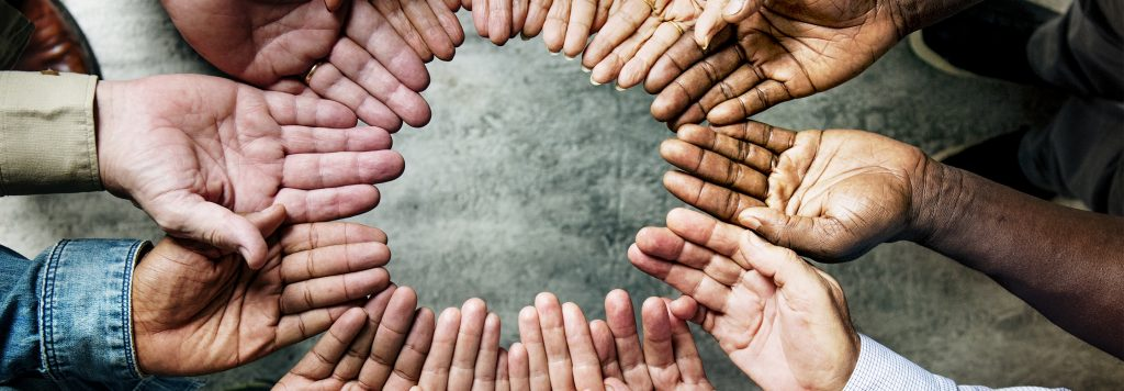 group of people making a circle with their open palms by standing together in a circle